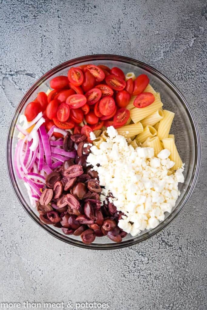 Bowl of tomatoes, onions, olives, feta, and noodles for pasta salad.