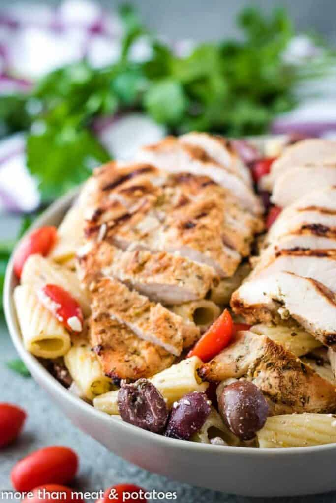 Gray bowl full of Greek pasta salad and sliced grilled chicken.
