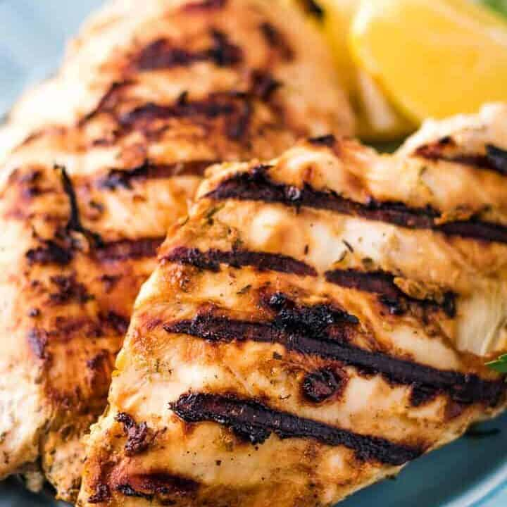 Two pieces of grilled chicken on a blue plate.