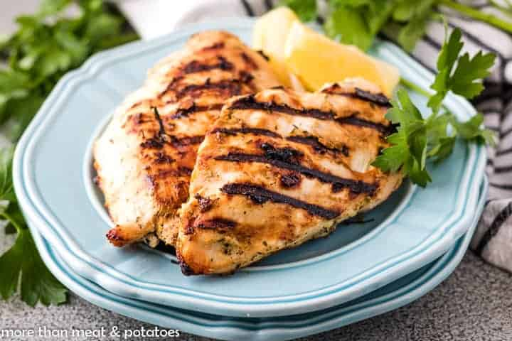 Two blue plates with two pieces of grilled chicken and parsley.