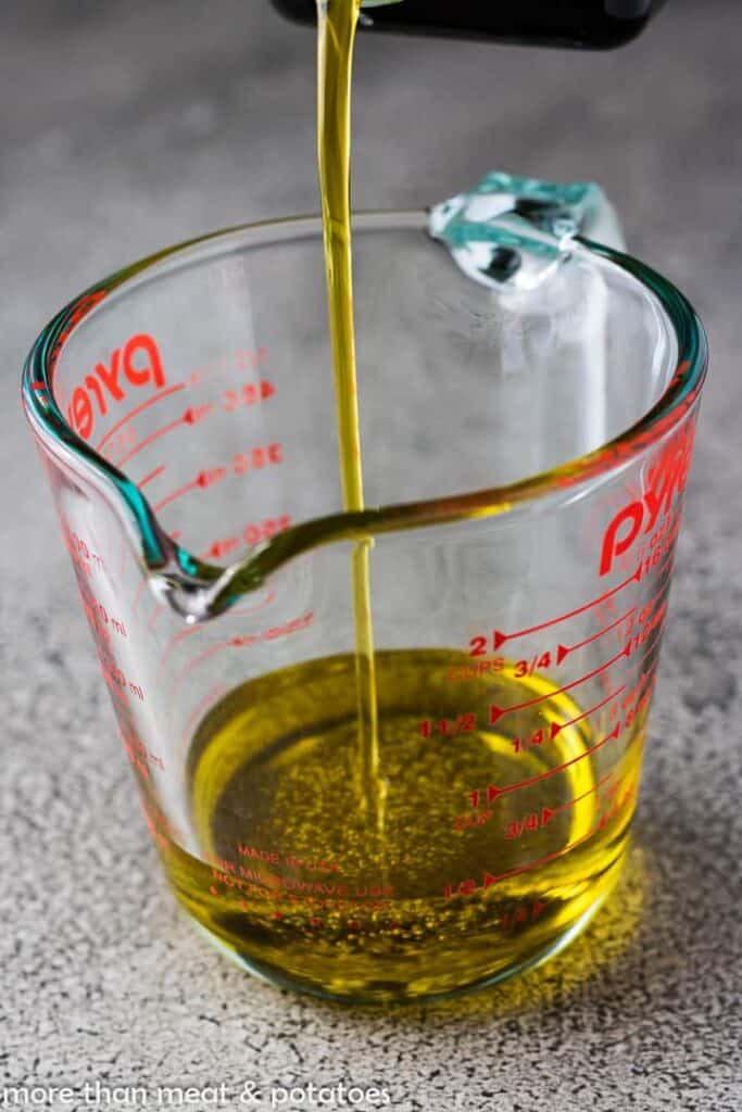 The olive oil being added to a measuring cup.