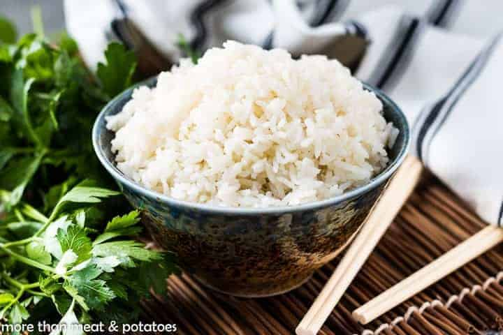 Coconut rice in a bowl next to parsley and chopsticks