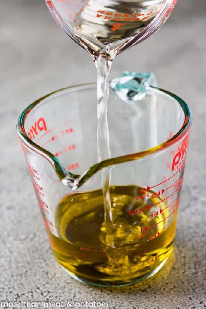 Pouring white wine vinegar into a measuring cup with olive oil.