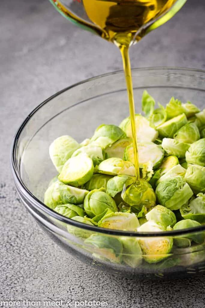 Brussels sprouts being drizzled with olive oil.