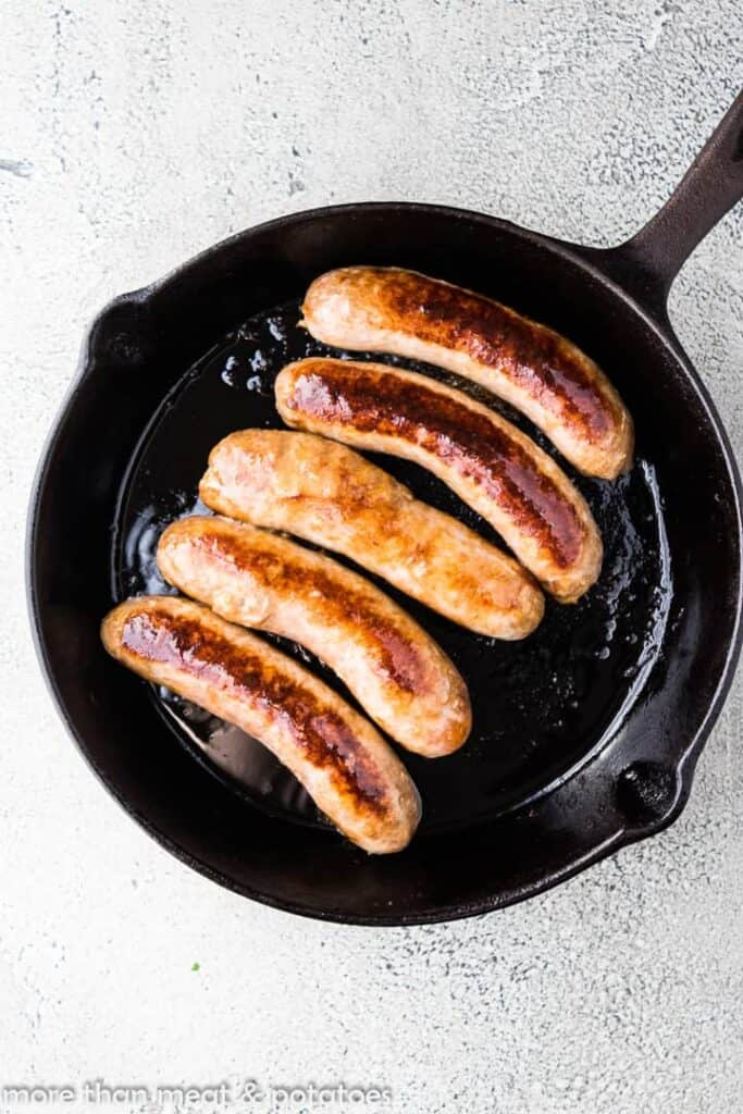 Five Italian sausage links cooking in a skillet.