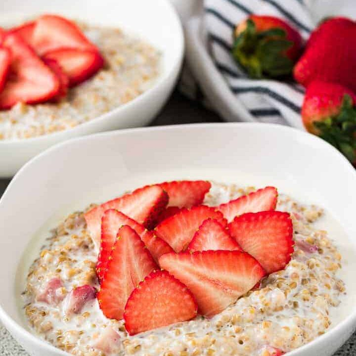 A bowl strawberry oatmeal topped with sliced strawberries.
