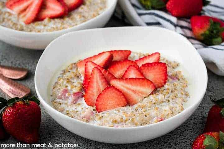 The strawberry oatmeal in a bowl topped with fresh strawberries.
