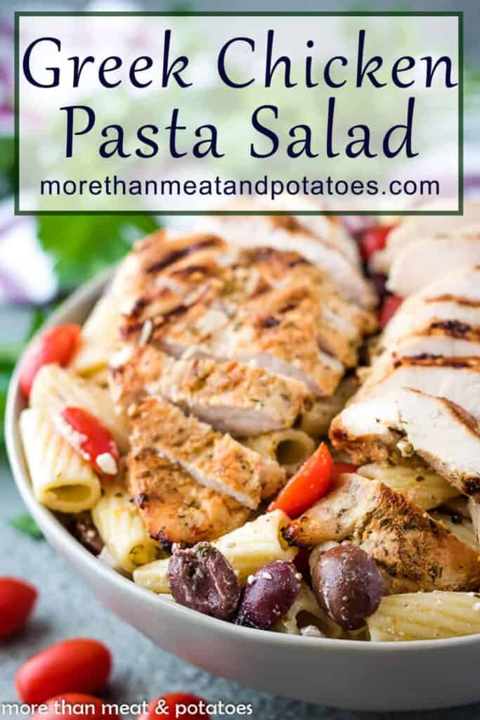 Sliced chicken over greek pasta salad in a large gray bowl.