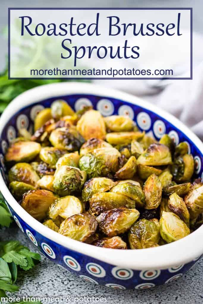 A colorful serving dish filled with oven roasted brussel sprouts.