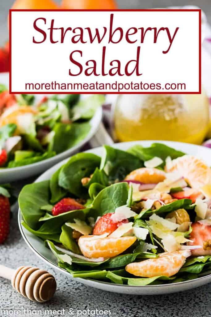 The spinach strawberry salad topped with orange wedges.