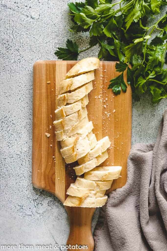 A sliced baguette on a wooden cutting board.
