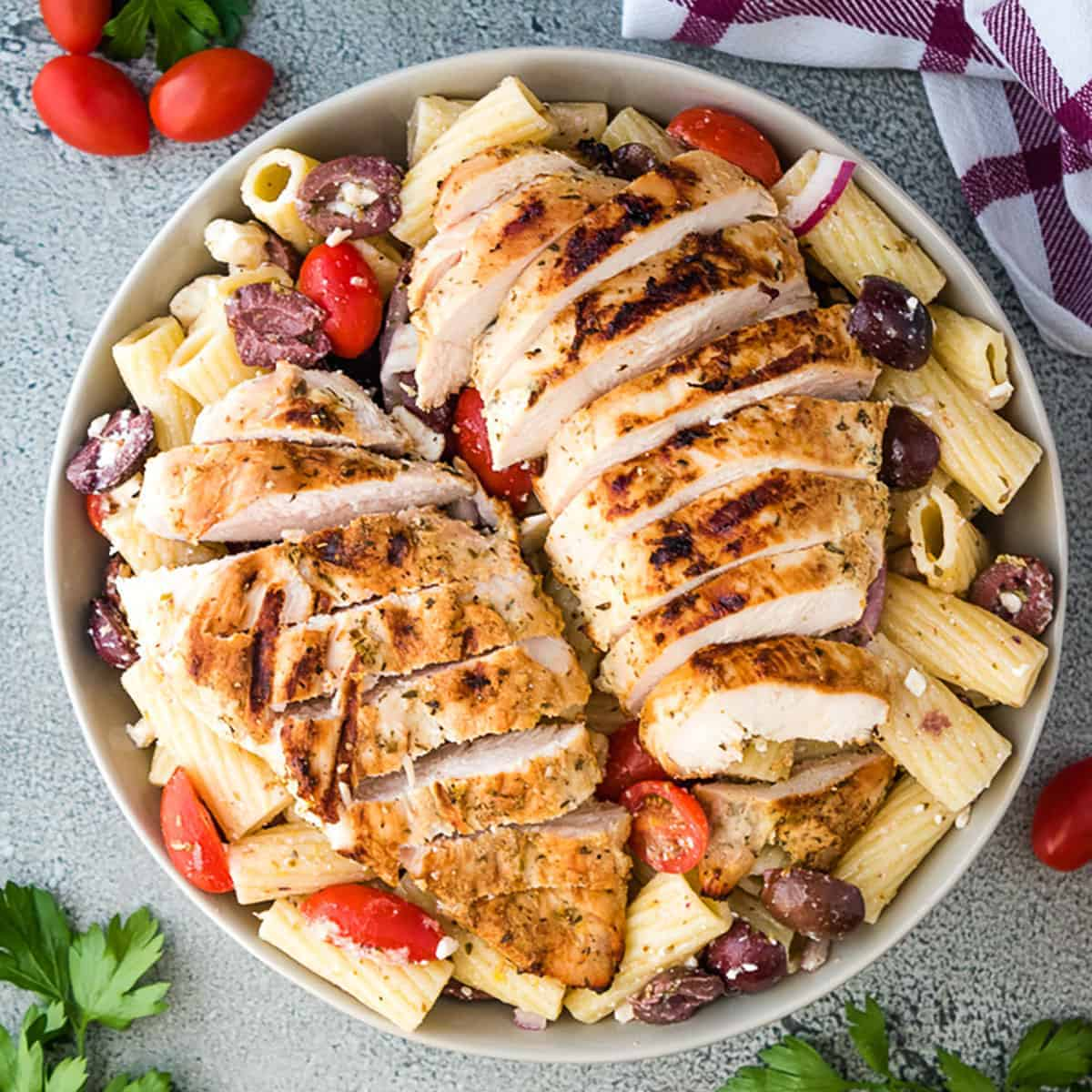 Top down view of sliced chicken breasts over Greek pasta salad.