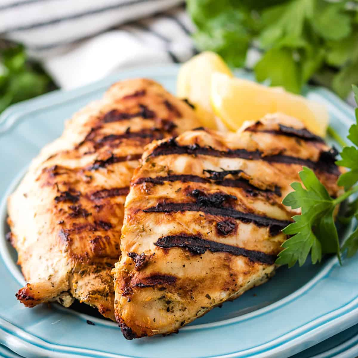 Perfectly grilled chicken on a blue plate with lemon slices.