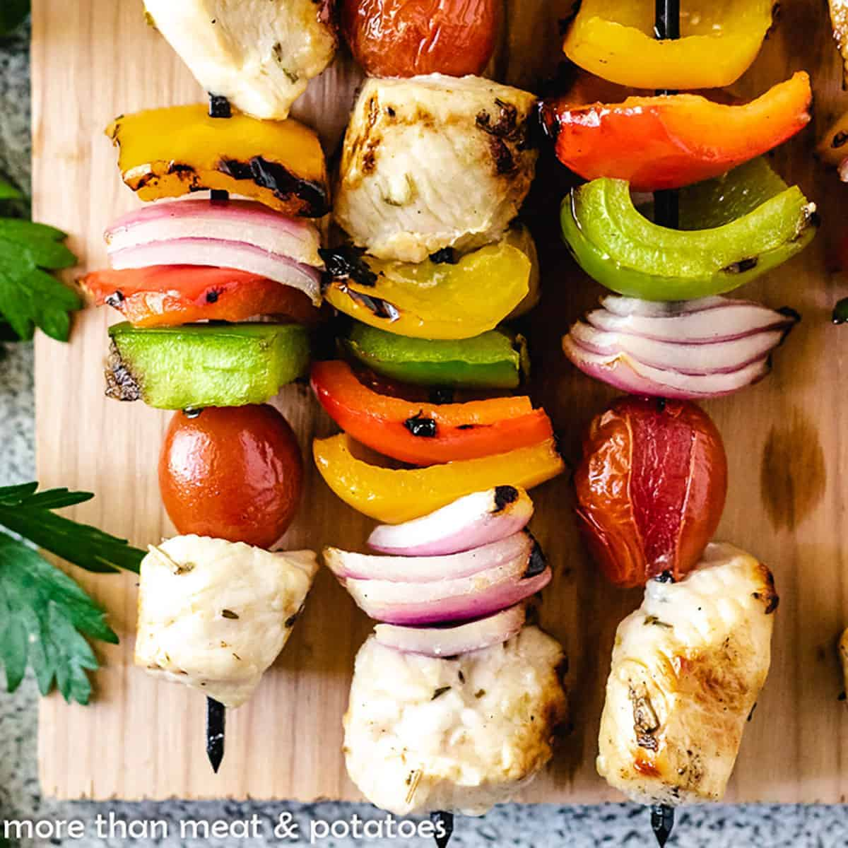 Three skewers with grilled chicken and vegetables on a cutting board.