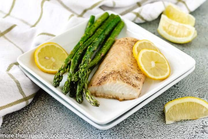 A piece of the oven baked mahi mahi served with lemon slices and asparagus.