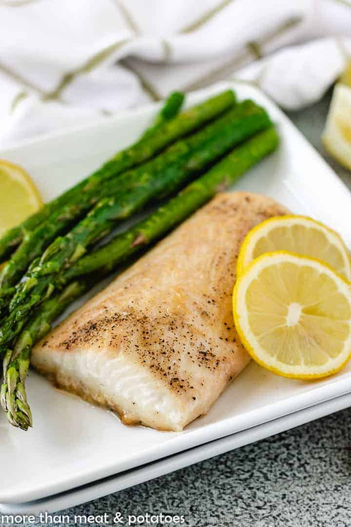 The fish steaks on a plate with fresh lemon slices and sauteed asparagus.