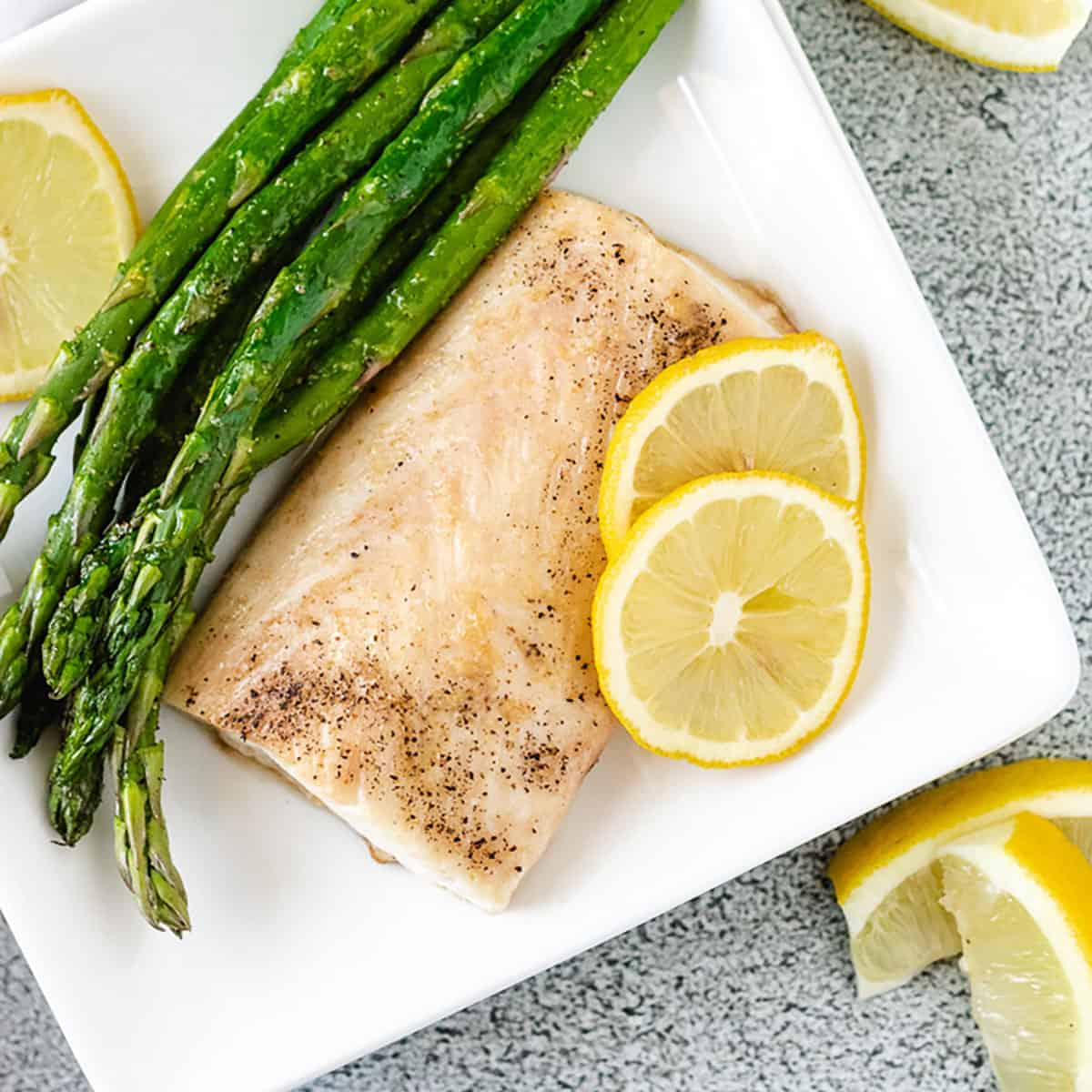 Top down view of a piece of Mahi Mahi new to sauteed asparagus and fresh lemon.