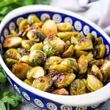 Blue oval dish filled with roasted brussel sprouts.