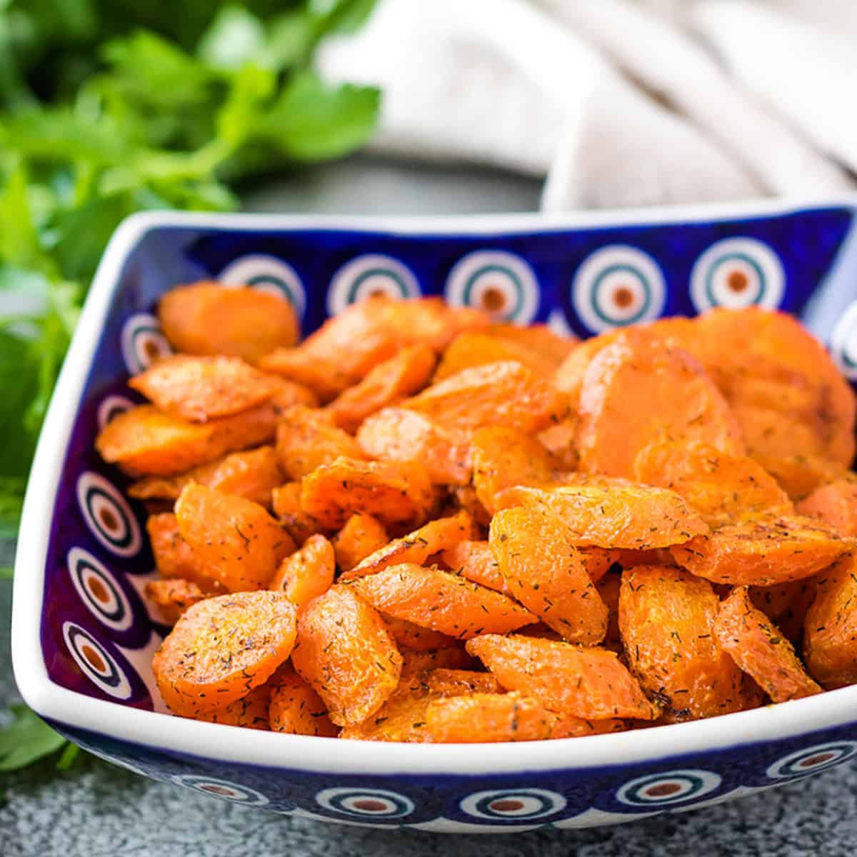 Blue square bowl filled with oven roasted carrots.