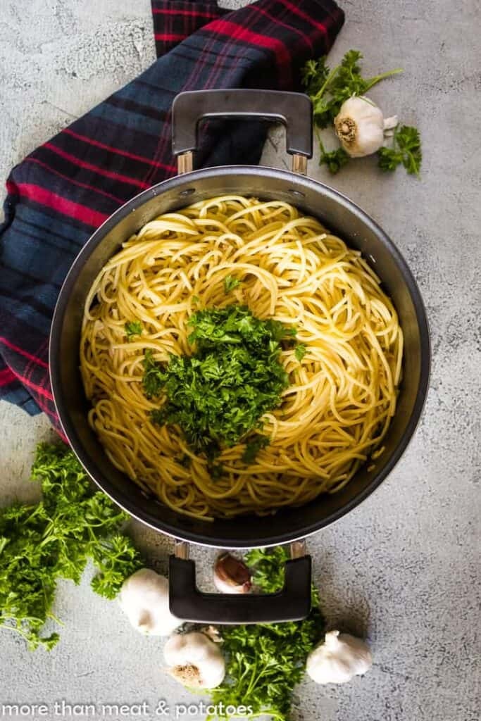 Cooked spaghetti tossed with oil mixture and topped with parsley.