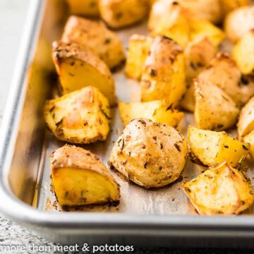 Diced and roasted potatoes on a sheet pan.