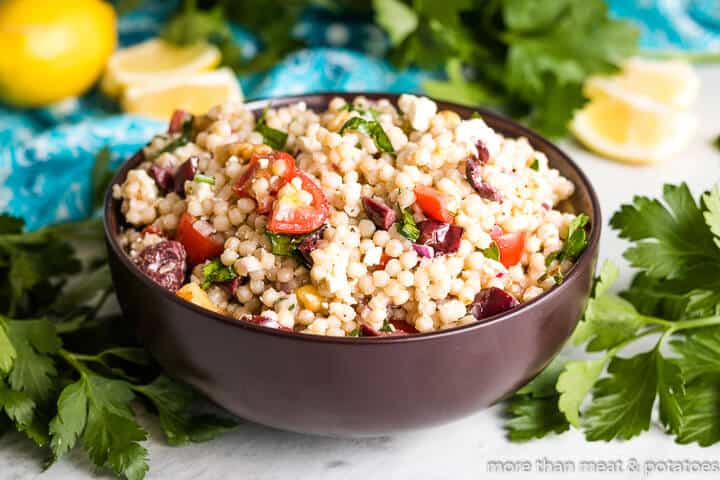 Lemon couscous salad in a bowl surrounded by lemons and parsley.