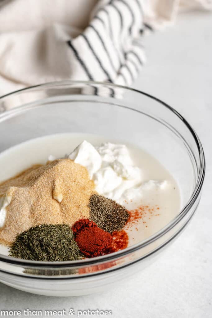 Buttermilk, sour cream, and spices in a mixing bowl.