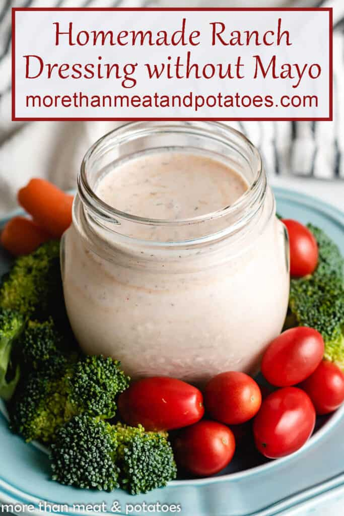 Homemade ranch dressing in a mason jar with fresh vegetables.