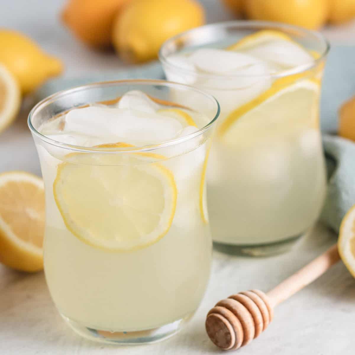 Two glasses with iced honey lemonade and fresh lemon slices.