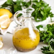 The lemon basil vinaigrette in a glass cruet.