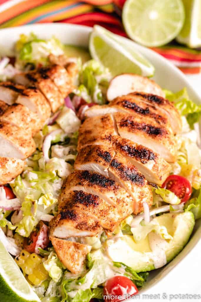 The sliced grilled poultry atop a bed of lettuce.
