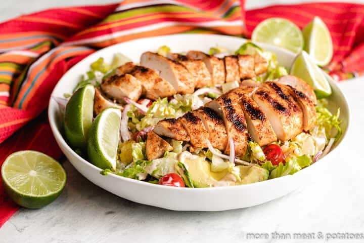Mexican grilled chicken salad served with lime wedges.