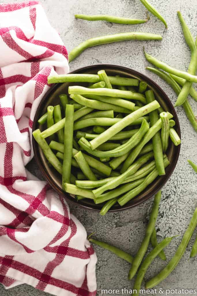 Fresh green beans with ends removed in a bowl.