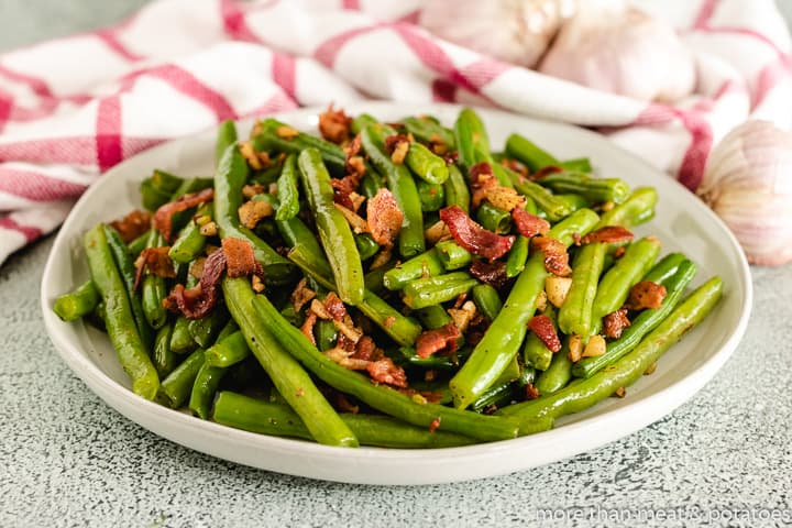 A pile of sauteed green beans topped with crispy bacon.
