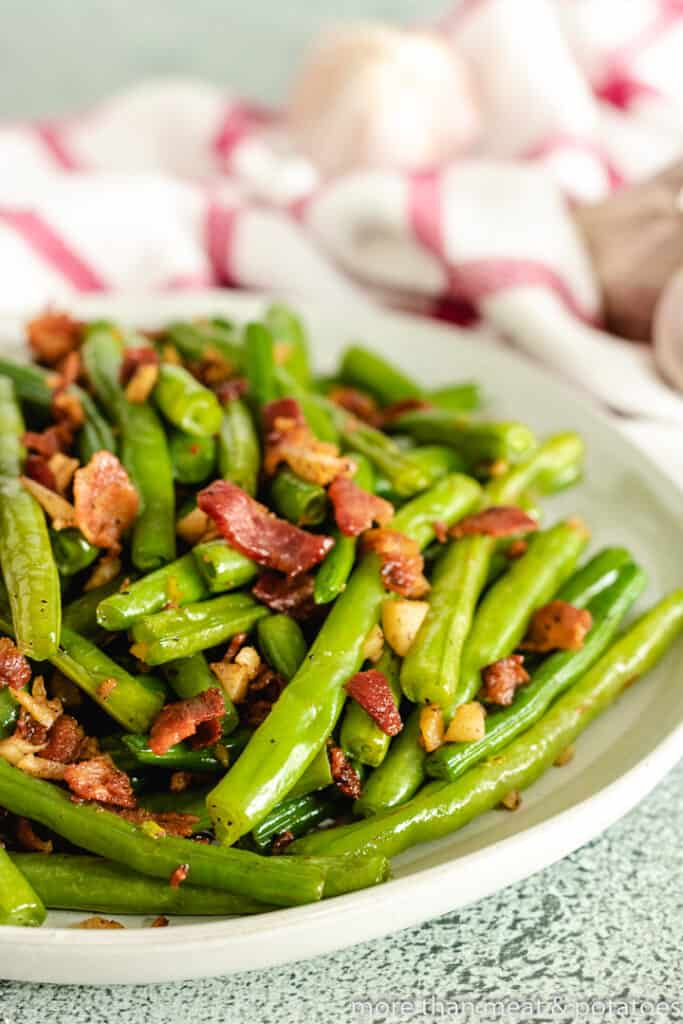 The finished green beans topped with bacon in a bowl.