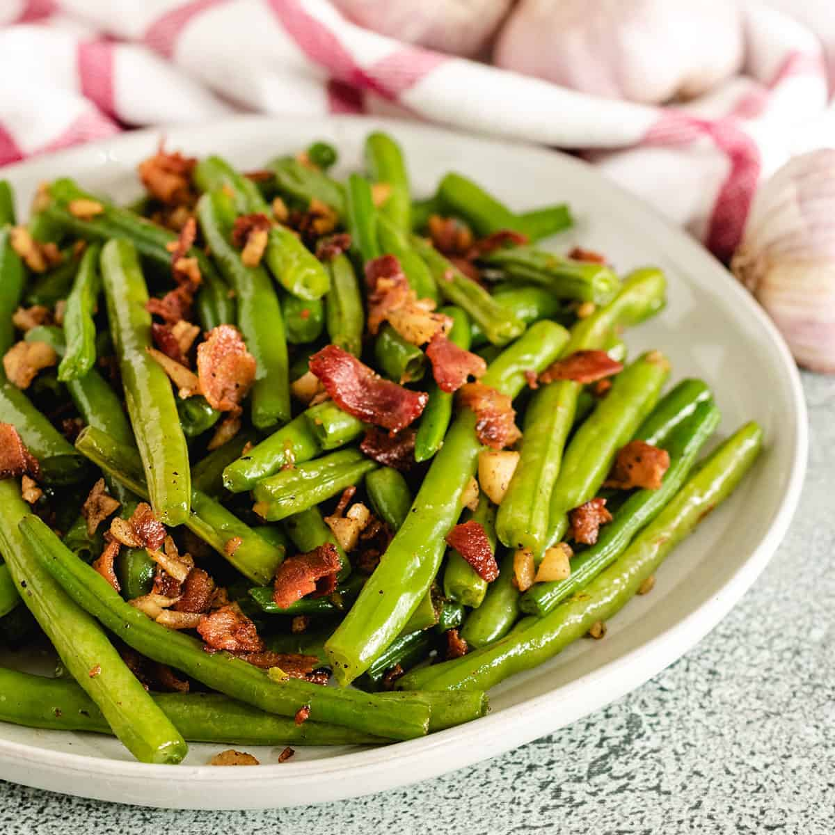 A big bowl filled with the sauteed green beans and bacon.