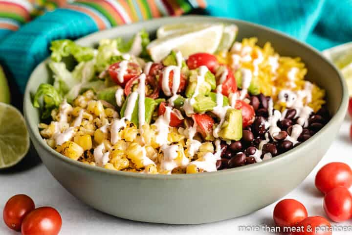 A side view of the colorful burrito bowl topped with chipotle sauce.