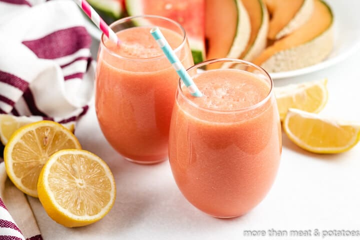 Two glasses of the watermelon cantaloupe juice with straws.