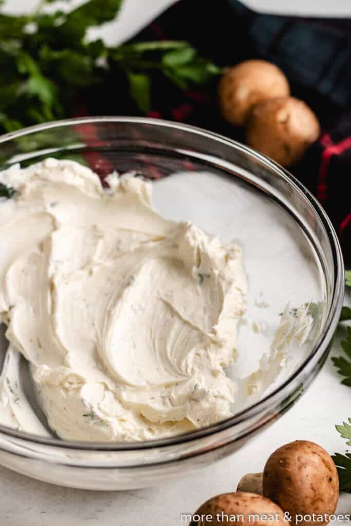Softened cream cheese in a mixing bowl with herbs.