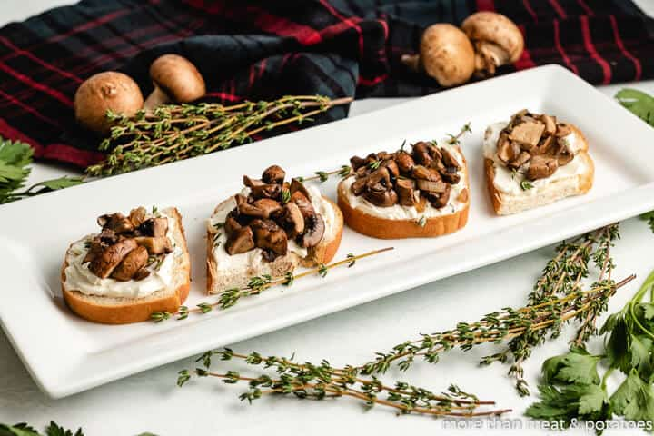 Four pieces of mushroom toasted garnished with fresh thyme.