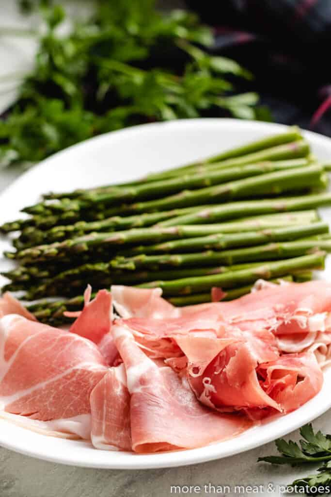 Prosciutto and asparagus spears on a plate.