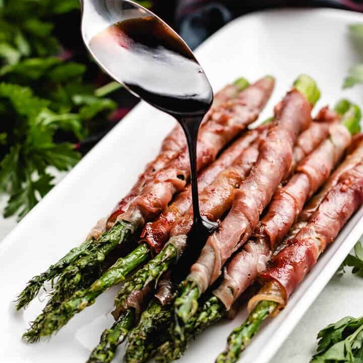The glaze being drizzled over the asparagus.