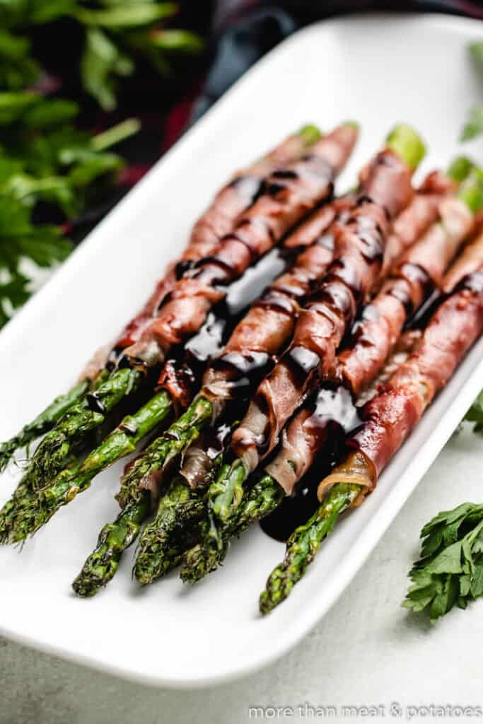 The grilled asparagus wrapped in prosciutto in a platter.