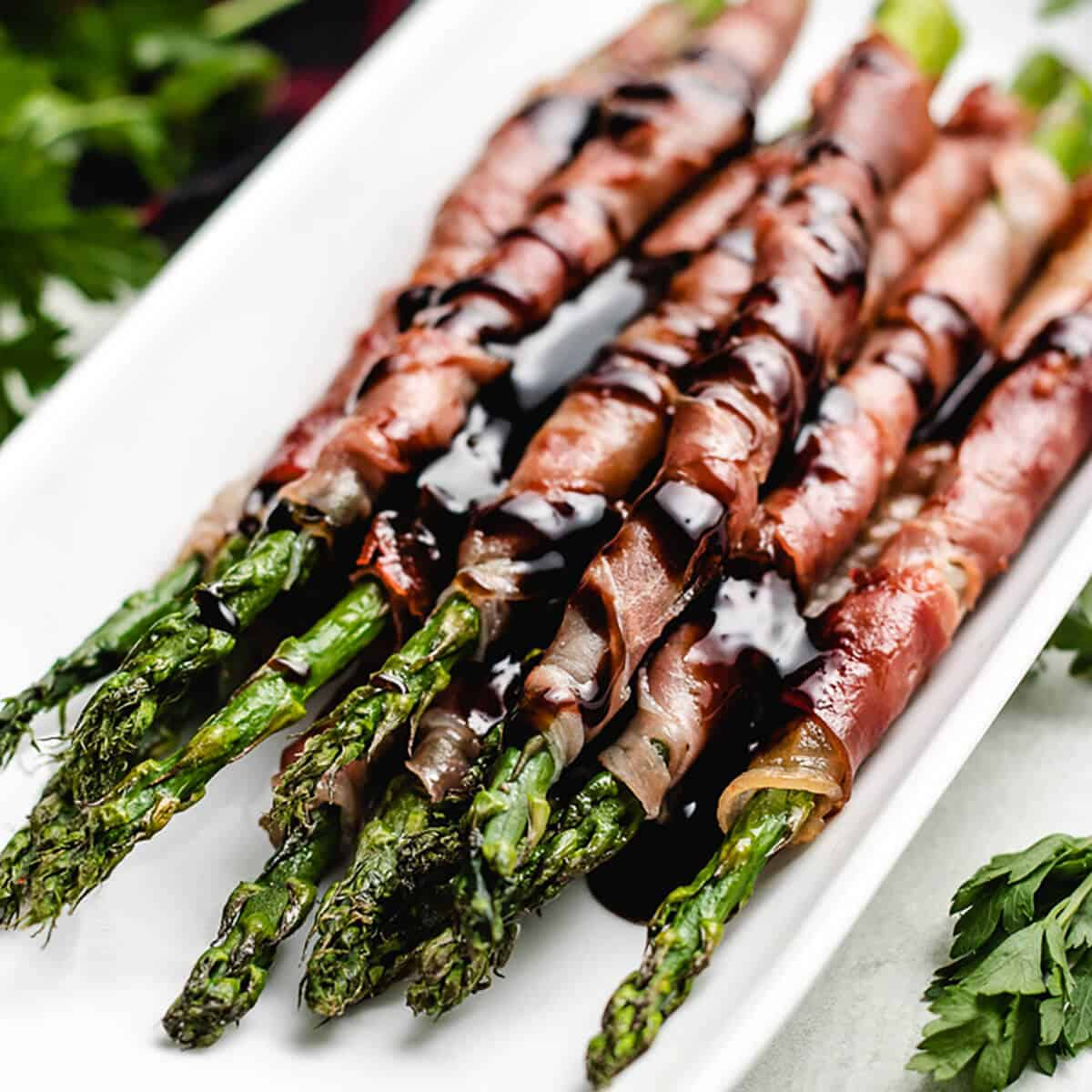 The prosciutto wrapped asparagus on a serving platter.