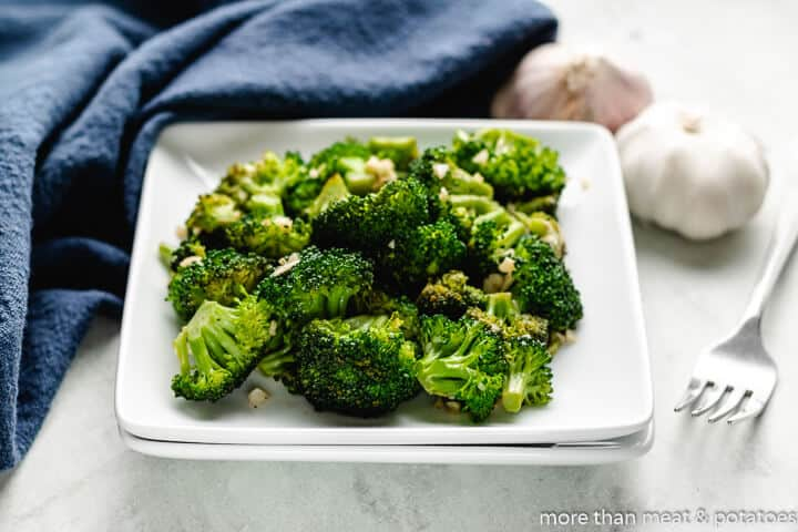 The sauteed broccoli and garlic served in a square bowl.