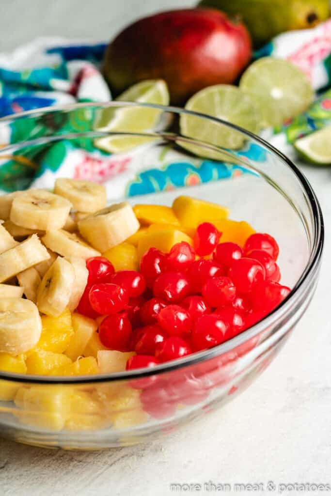 Cherries and sliced bananas and pineapples, in a mixing bowl.