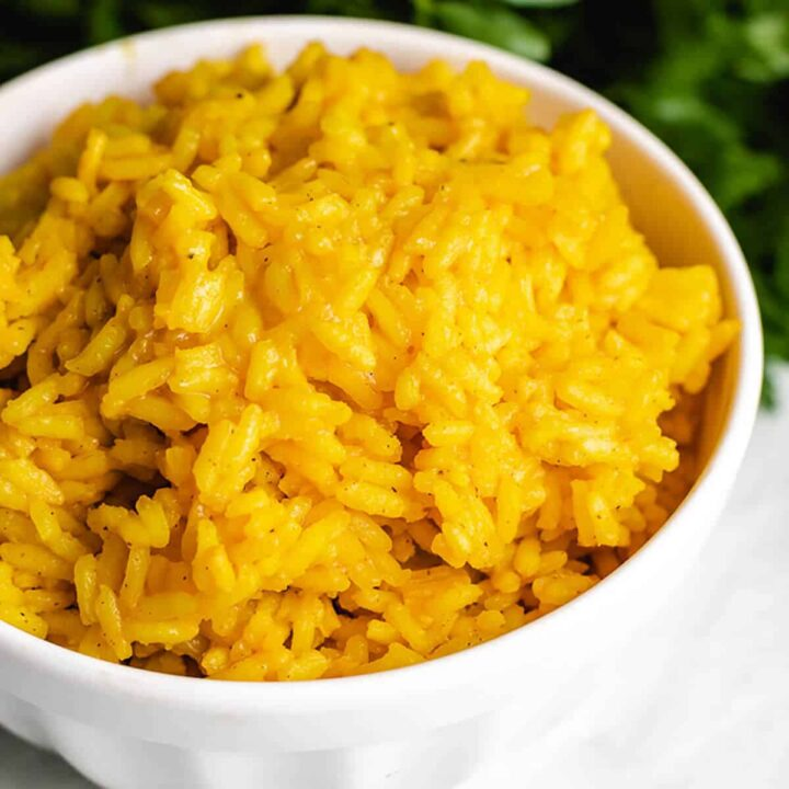 The finished yellow rice served in a white bowl.
