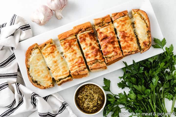 Top-down of the sliced cheesy pesto garlic bread.