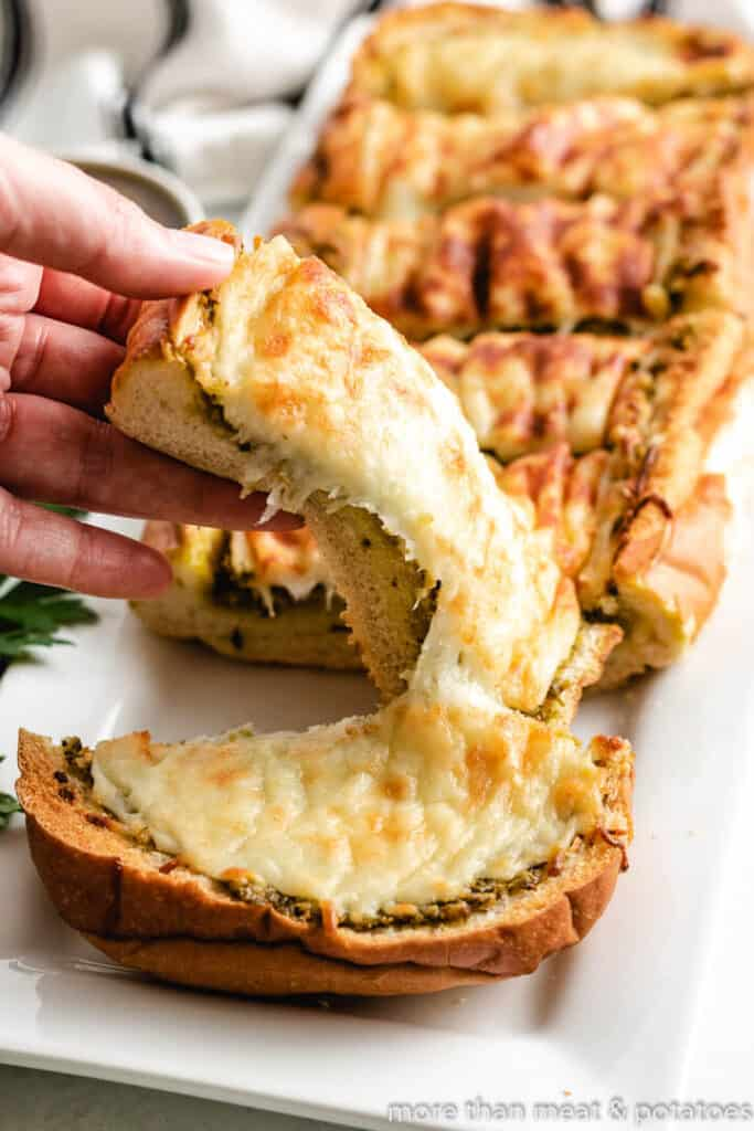 A slice of the cheesy pesto bread being lifted from the plate.