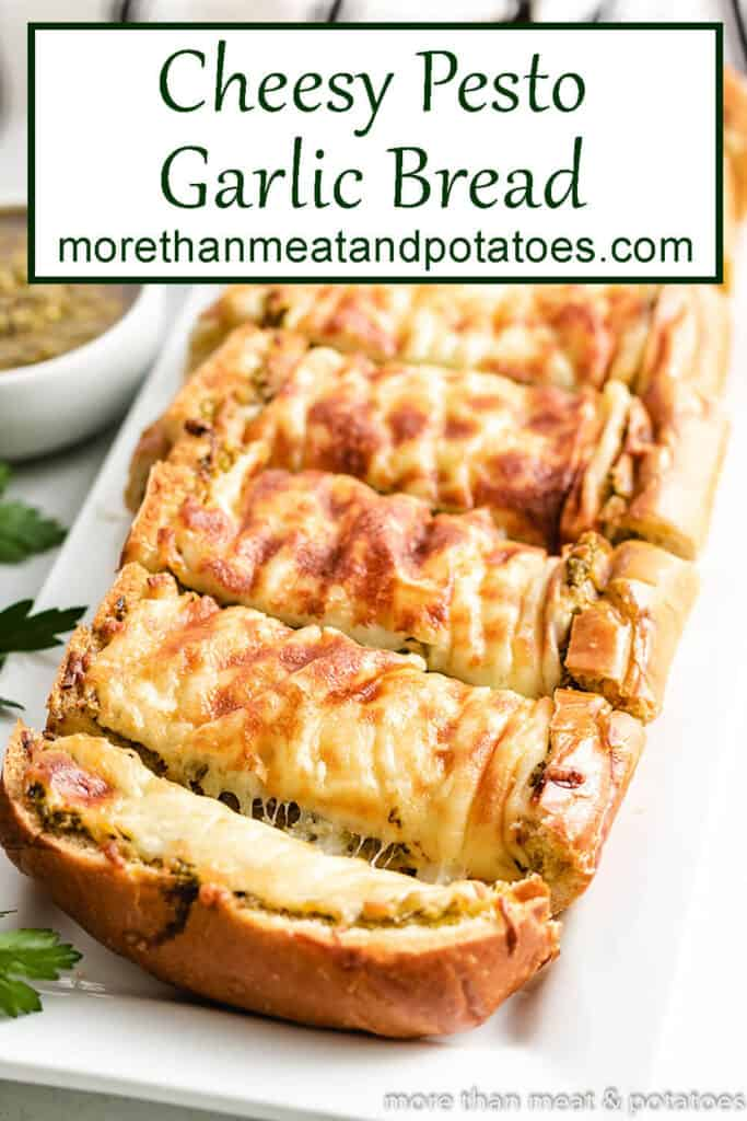 Angled view of the baked pesto garlic bread topped with cheese.